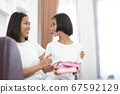 Asian little girl giving her mother a gift at home 67592129