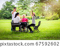 Happy asian family in outdoor park,father,mother with little child girl or daughter play,dancing,elderly woman having fun,laugh,smile together,senior grandmother in wheelchair with her family in summe 67592602