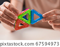Close up of magnetic building toy. WOman playing with preschooler.  67594973