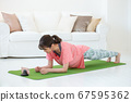 스마트 폰을 보면서 집에서 훈련을하는 젊은 여성 67595362