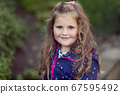 happy cute little girl with curly golden hair 67595492
