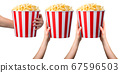 Woman hand holding striped bucket with popcorn isolated on white background 67596503