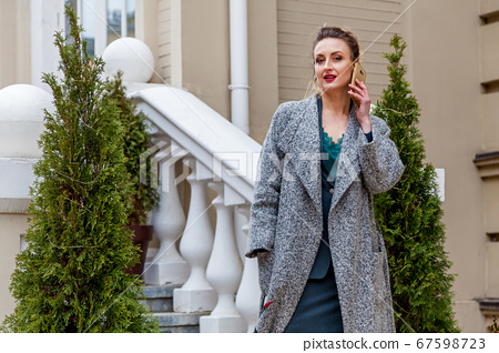 An attractive woman with a mobile phone in front 67598723