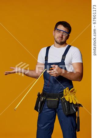 repairman worker in uniform holding measure tape. 67601173