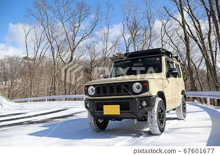 四輪驅動的微型汽車在雪道上行駛。 67601677