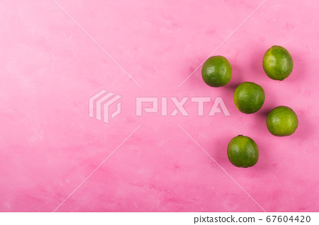Fresh whole green limes on pink background 67604420