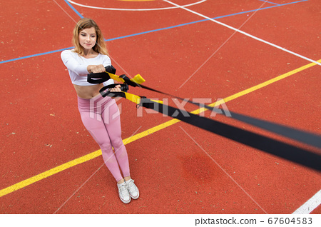 Pretty young Caucasian girl in pink sportswear exercising with suspension trainer sling, doing squats, outdoors at red sport court. Fitness concept with trx trainer 67604583