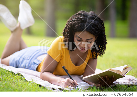 Black female student taking notes from textbook on picnic blanket in park 67604654
