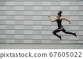 Excellent training running. African american girl in sportswear froze in air above ground, jumping 67605022