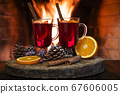 Two glasses of hot mulled wine with spices on the background of fireplace. 67606005