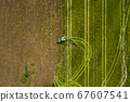 Aerial: The tractor harvester on the agricultural field 67607541