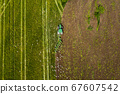 Aerial: The tractor harvester on the agricultural field 67607542