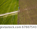Aerial: The tractor harvester on the agricultural field 67607543