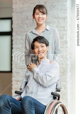 男人和女人夫婦坐在輪椅上 67608477