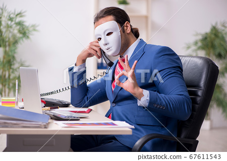Male employee with mask in hipocrisy concept 67611543
