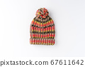 Multicoloured winter woolen hat with pompon isolated on white background. Flat lay. Top view 67611642