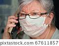 Elderly senior woman with glasses wearing hand 67611857