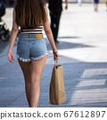 Closeup of girl wearing a mini blue jeans short  67612897