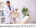Young male doctor with skeleton 67612971