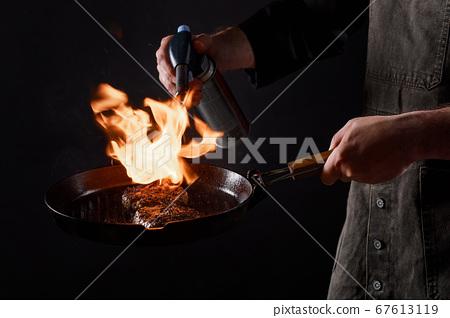 Cef cooks burgers, roasts meatballs on open fire. 67613119