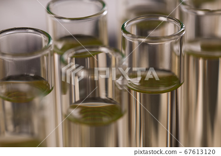 Test tubes in special handles with yellow liquids 67613120