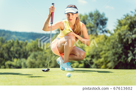 Woman on golf course taking measure on the green 67613602