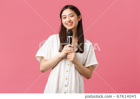 Leisure, people emotions and lifestyle concept. Cheerful smiling asian girl in karaoke, enjoying weekends, singing song in microphone, perform stand-up, standing pink background 67614045