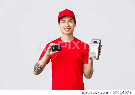 Smiling friendly courier in red uniform t-shirt and cap, advice pay for food delivery or orders with credit cards using payment terminal. Delivery guy show POS paying method, standing grey background 67614078