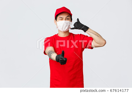 Call out customer support anytime. Cheerful asian delivery guy in medical mask and protective gloves, wink and show thumb-up, phone sign, provide safe courier service. carrier and shopping concept 67614177
