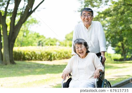在輪椅上公園散步的年長夫婦 67615735