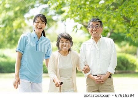 年長的夫婦和照料者在公園散步 67616294