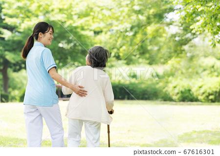 高級女子和照顧者在戶外康復後視圖 67616301