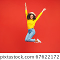 happy ethnic girl in a summer hat jumps on a  red 67622172