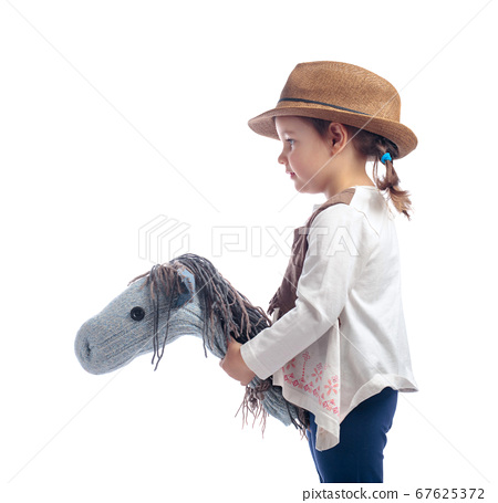 Cute little girl dressed like a cowboy playing 67625372