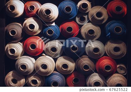 many textile rolls of blue, white and orange 67625522