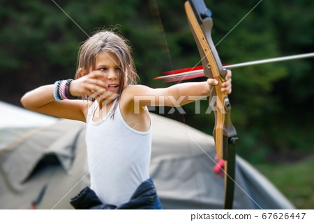Gipsy girl enjoying with the arrow leaving the bow 67626447