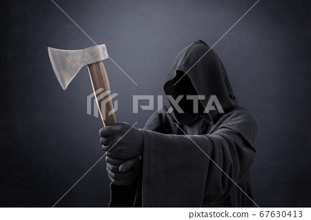 Scary figure in hooded cloak with axe in the dark 67630413