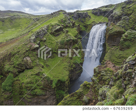 Beautifull waterfall on the Skoga River with rainbow and no people on famous Fimmvorduhals trail second part of Laugavegur trek. Summer landscape on a sunny day. Amazing in nature. August 2019, South 67639269