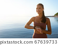Happy healthy woman running on the beach, using tracker 67639733