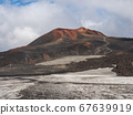 Red and black volcanic Iceland landscape at Fimmvorduhals hiking trail with glacier volcano lava field, snow and magni and mudi hill, createed by eruption of Eyjafjallajokull in 2010 which affected 67639919