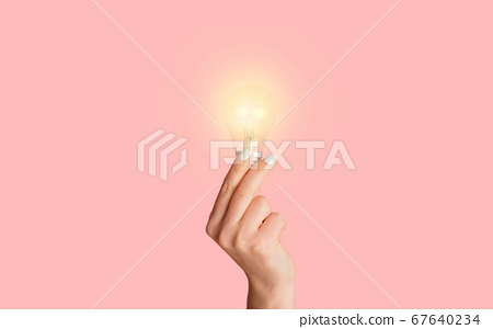 Creative idea concept. Young woman holding shining light bulb on pink background, closeup 67640234