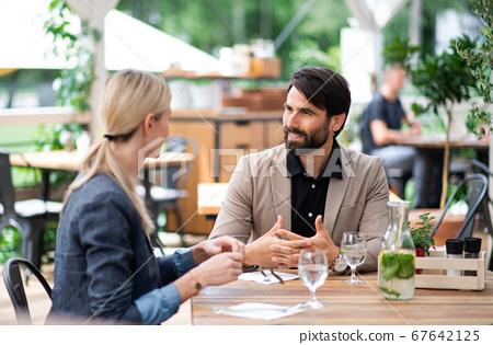 Happy couple sitting outdoors on terrace restaurant, talking. 67642125