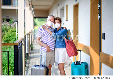 Senior couple with face masks and luggage outside apartment on holiday. 67642163