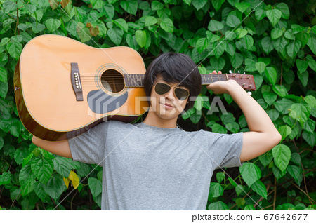 The guy is holding the guitar, outdoo, cargo pants 67642677