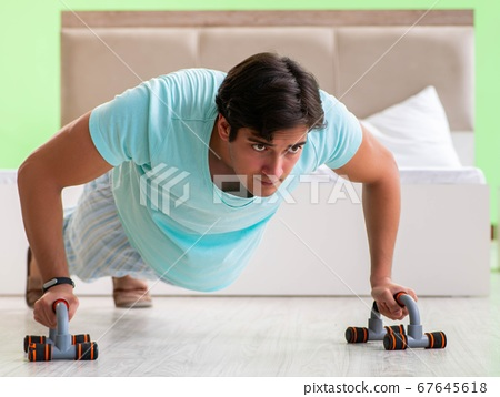 Young man in pajamas doing morning exercises 67645618