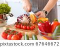 Man in apron cutting orange in kitchen 67646672