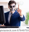 Businessmsn with scary face mask working in office 67649750