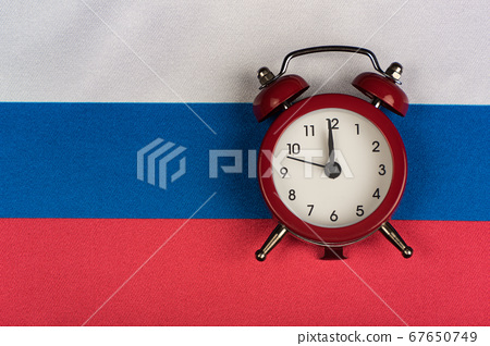 Russian Federation flag and vintage alarm clock 67650749
