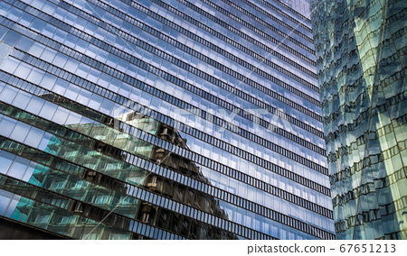 Glass Facade Of Modern Office Buildings With Reflections Of Neighboring Towers In The City Of Vienna 67651213