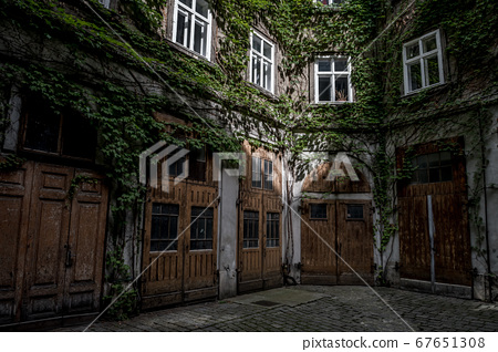 Courtyard Of A HIstoric Building With Wooden Doors And Ivy Overgrown Walls 67651308